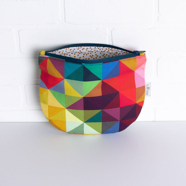 tullibee jules rainbow geometric triangle midi round pouch propped against a white brick wall with zip top open & view of mustard spot lining