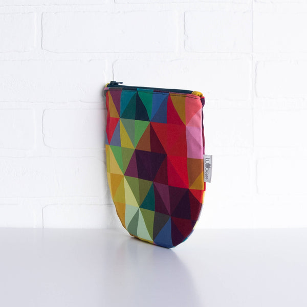 tullibee jules rainbow geometric triangle midi round pouch propped upright against a white brick wall at an angle to show the depth of the pouch