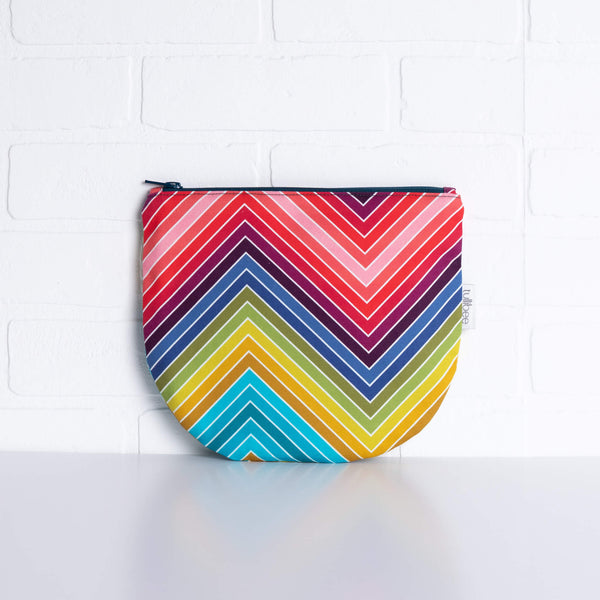 tullibee marni rainbow zig-zag midi round pouch propped against a white brick wall (front view)