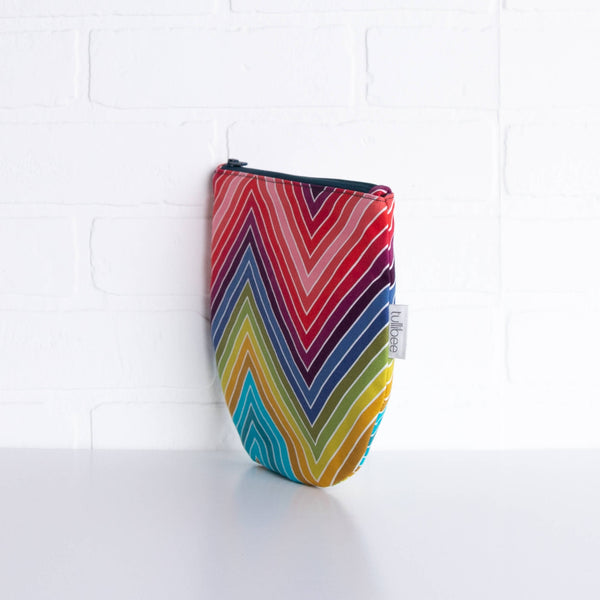 tullibee marni rainbow zig-zag midi round pouch propped upright against a white brick wall at an angle to show the depth of the pouch