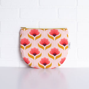 tullibee mini margot retro floral midi round pouch propped against a white brick wall (front view)
