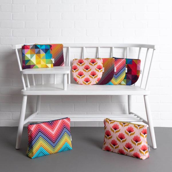 tullibee pouches midi, midi round & maxi sizes all fabric designs on a white ercol telephone bench along in front of a white brick wall