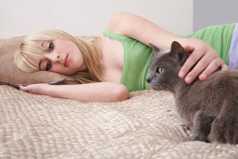 cat and woman on a bed