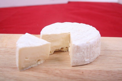 round of brie cheese with a slice removed