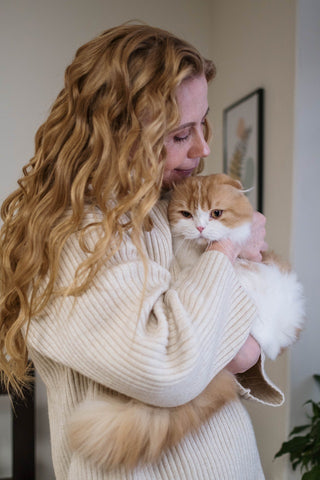 woman holding a large orange and white cat