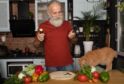 man showing vegetables to his cat