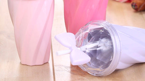 Belle bow cup image shows 3 cup colors: blush pink, fuchsia & lavender, on a hardwood floor. The lavender cup is on its side, showing off the signature bowtie sippy straw with transparent spill proof lid.