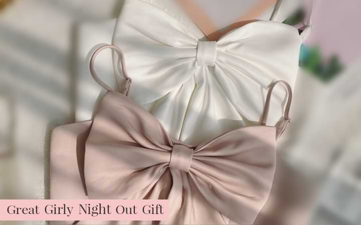Pink and white Belle Bow Camisole Crop Tops on bed, in shadow. Great girly night out gift: sisterhood, bridal party