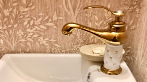 Brass Coco glam faucet with white ceramic core on polished white square sink. Textured wallpaper shows light browns and tans in detailed grass and leaf patterns, depicting forestry.