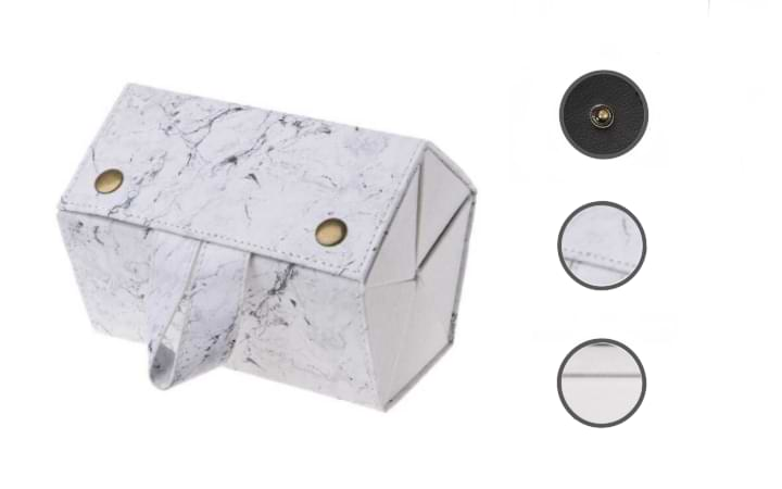 White Marble Foldable Sunglasses Case rolled into tote mode. Circular cut-outs show the copper button, leather exterior, and the flannel lining.