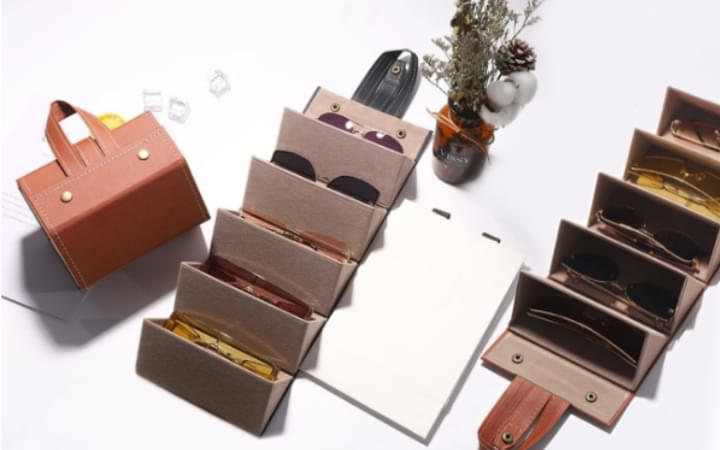 Brown Foldable Sunglasses Case folded into tote form, next to black and brown unfolded cases. Each deck of the case houses a different pair of eyewear., showing 10 in all.