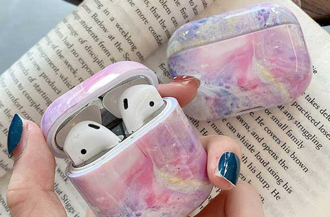 Purple Fuschia pink Marble airpod case held in hand. Airpods snug and secure in case