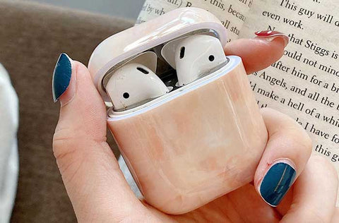 Peach toned airpod silicone case cover in hand over desk with book