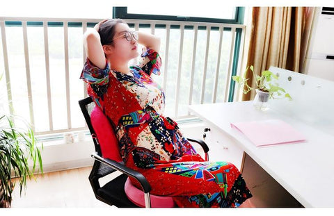 Woman in patterned red print dress leans back relaxing, hands clasped behind her head with her eyes closed. Seated on fuchsia Shiloh seat cushion on black mesh chair at a desk in a sunny room