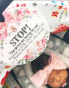 Just born little girl in her car seat with a flower no touching baby sign