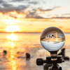 Lensball Australia - Brushed Gold Lensball Stand in front osf sunset