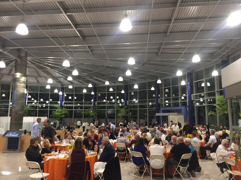 A car dealership's lobby is transformed into a fundraiser even with many tables and people sitting at them.