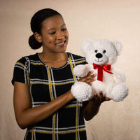 A woman holds a white bear that is 10.5 inches tall while sitting