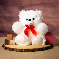 A white bear that is 11 inches tall while standing sitting on a piece of wood