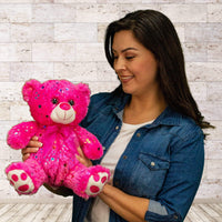 A woman holds a  sparkly pink bear that is 10 inches tall while sitting