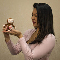 A woman holds a brown monkey that is 4 inches tall while sitting