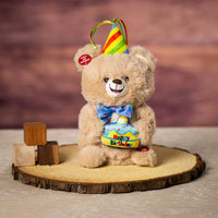 A beige musical bear that is 10 inch tall while sitting on top of a piece of wood