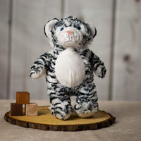A black and white stripped tiger that is 15 inches tall while standing on top of a piece of wood