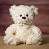 A cream bear that is 11 inches tall while sitting