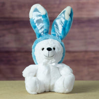 A white bear that is 9 inches tall while sitting wearing blue bunny ears that are 7 inches tall