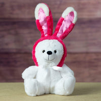A white bear that is 9 inches tall while sitting wearing magenta bunny ears that are 7 inches tall