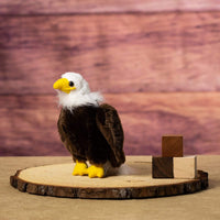 A eagle that is 10 inches tall while standing on top of a piece of wood