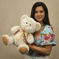 A woman holds a beige bear that is 14 inches tall while sitting