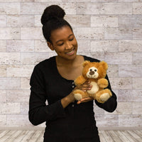 A woman holds a brown bear that is 7 inches tall while sitting