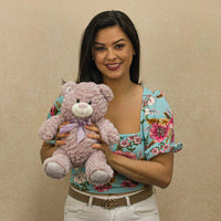 A woman holds a lavender bear that is 10 inches tall while sitting