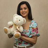 A woman holds a beige bear that is 10 inches tall while sitting