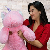 A woman holds a laying pink unicorn that is 40 inches from head to tail