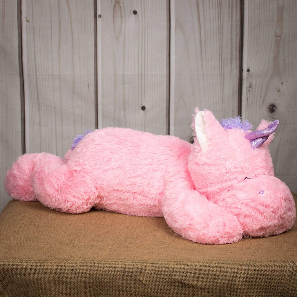 A laying pink unicorn that is 40 inches from head to tail