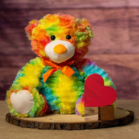 A fuzzy rainbow bear that is 12 inches tall while sitting on top of a piece of wood