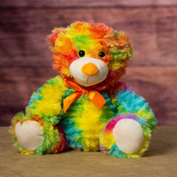 A fuzzy rainbow bear that is 12 inches tall while sitting
