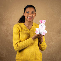A woman holds a white bunny with pink ears and feet that is 6 inches tall while sitting