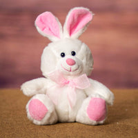 A white bunny with pink ears and feet that is 6 inches tall while sitting