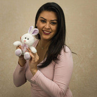 A woman holds a white bunny with purple ears and feet that is 6 inches tall while sitting