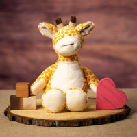 A giraffe that is 12 inches tall while standing in a sitting position on a piece of wood