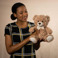 A woman holds a beige bear that is 11 inches tall while sitting