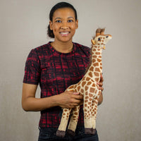A woman holds a  spotted giraffe that is 19 inches tall while standing