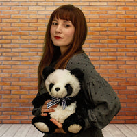 A woman holds a black and white panda that is 11 inches tall while sitting