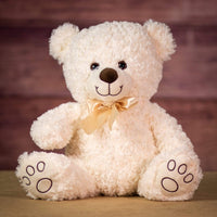 A white bear that is 12 inches tall while sitting with paw prints on its feet