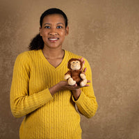 A woman holds a brown yelling monkey that is 5 inches tall while sitting