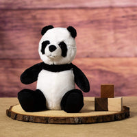 A black and white panda that is 9 inches tall while sitting on top of a piece of wood