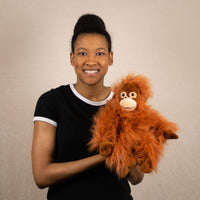 A woman holds a orange orangutan that is 10 inches tall while sitting